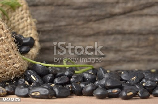 Black bean in burlap bag on old wooden background, close up ,concept of healthy protein power,select focus