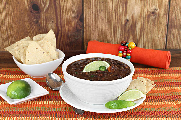 Black bean mexican soup with chips and lime. stock photo