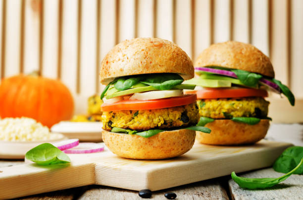 black bean millet pumpkin burgers with spinach leaves on a wood background stock photo