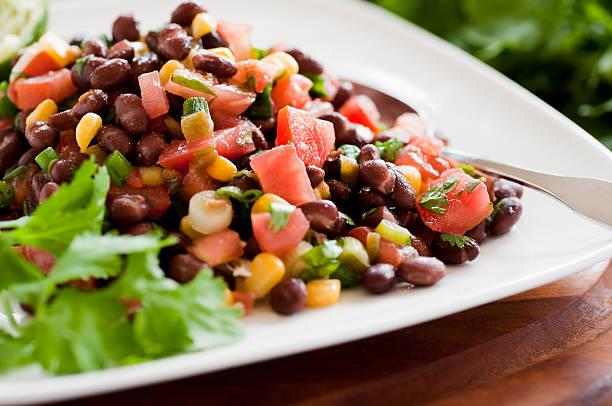 Black bean salad on white plate siting horizontally on table stock photo