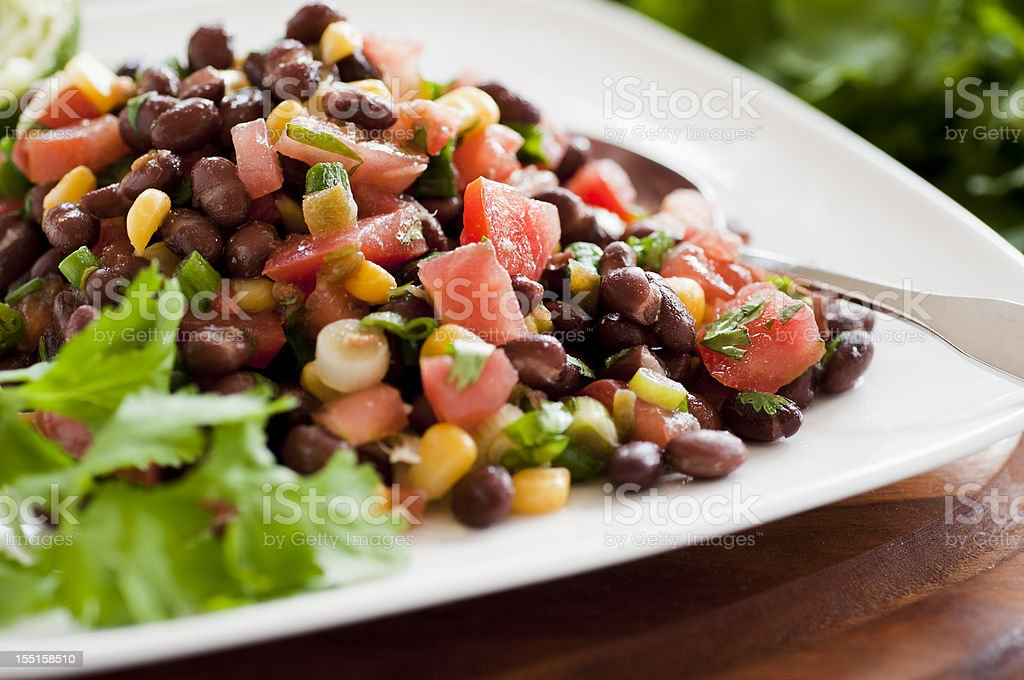 Black bean salad on white plate siting horizontally on table stock photo