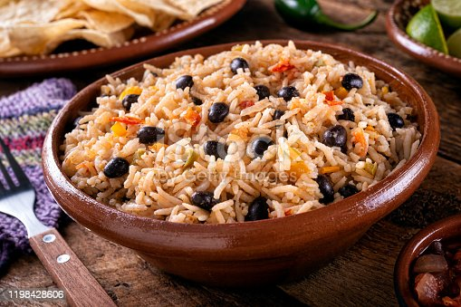 A bowl of delicious black beans and rice on a rustic table top.