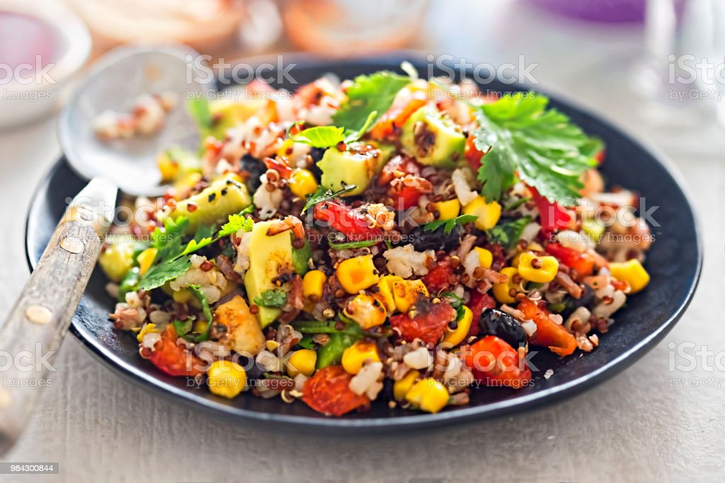 Black beans, avocado, corn, tomato, rice & quinoa salad with chilli dressing stock photo
