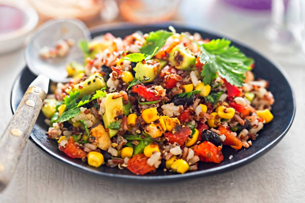 black beans, avocado, corn, tomato, rice & quinoa salad with chilli dressing - quinoa stock photos and pictures