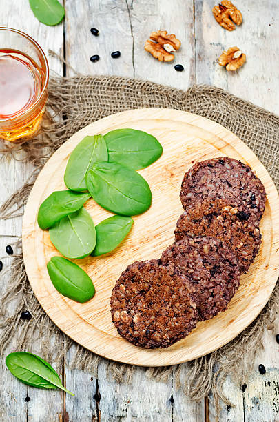 black beans brown rice walnut oat burgers with spinach stock photo