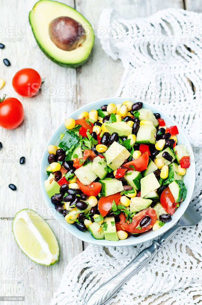 Black beans corn avocado cucumber tomato salad with lime dressing stock photo