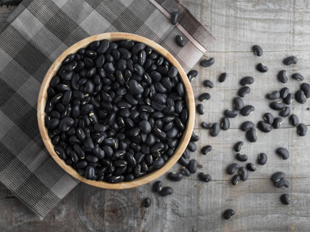 Black beans in a wooden bowl, black beans in a wooden spoon on a wood background stock photo