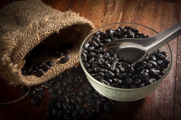 Black Beans in bowl and metal spoon with sack. stock photo
