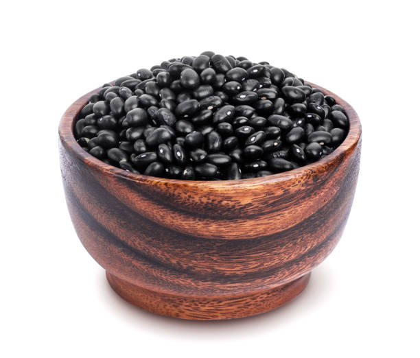 Black beans in wooden bowl isolated on white background stock photo