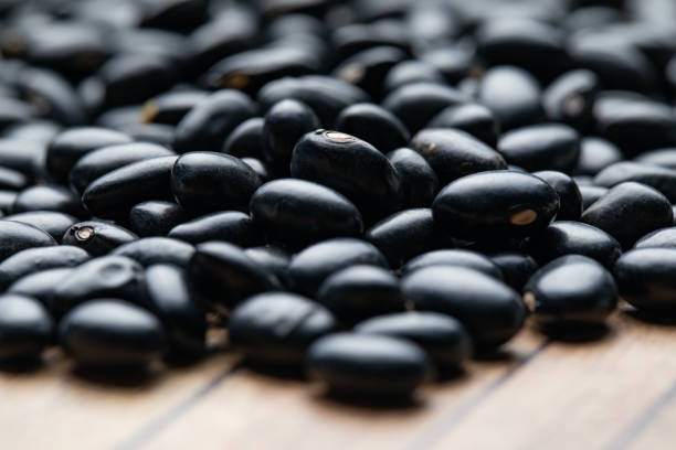 black beans on wooden table (focus and macrophotography) - low contrast stock pictures, royalty-free photos & images