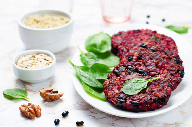 Black beans quinoa beet walnuts burgers with spinach stock photo