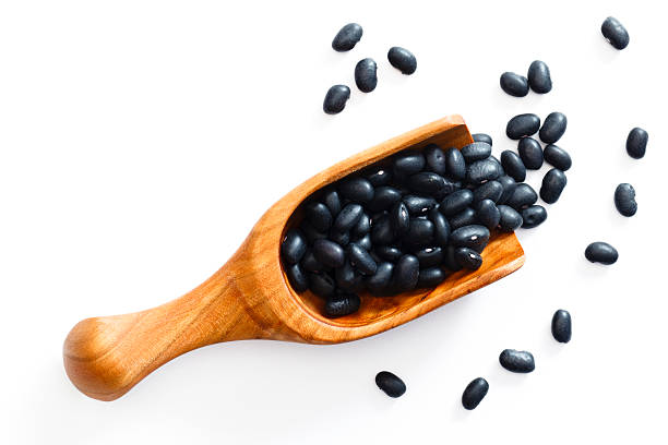 Black beans spilling from a wooden scoop stock photo