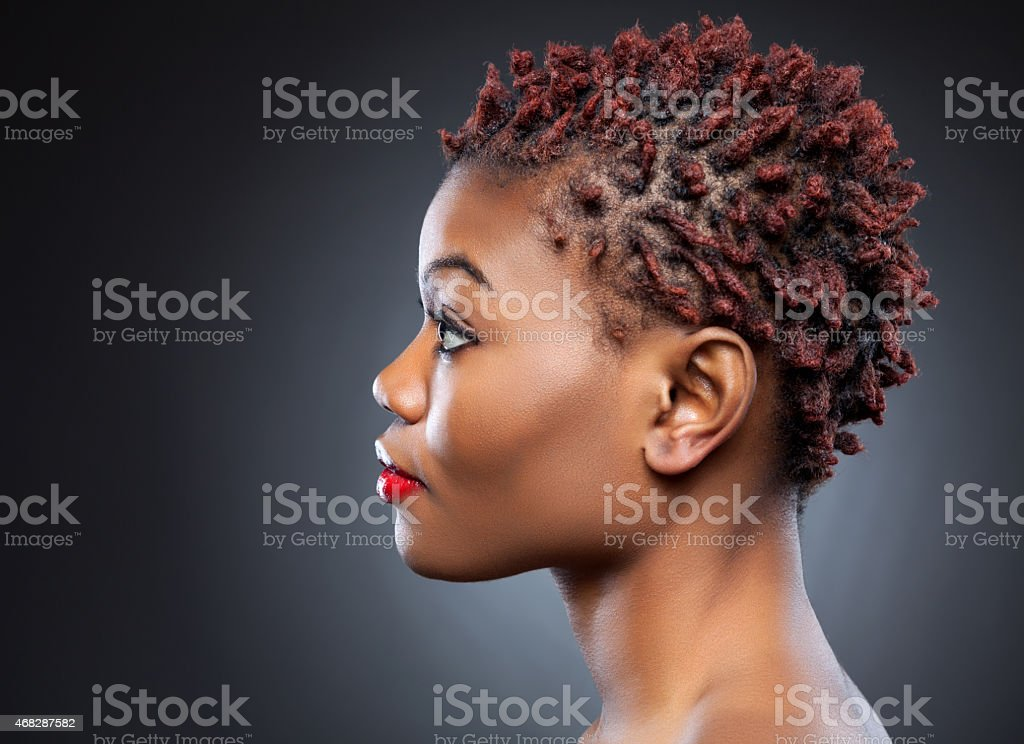 A black beauty with spiky short hair in a dark background stock photo