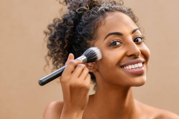 Black beauty woman using makeup brush Closeup portrait of african woman applying foundation with makeup brush. Black beauty girl gets blush on the cheek isolated on background. Portrait of attractive young woman looking at camera while using makeup brush for face powder. blusher make up stock pictures, royalty-free photos & images