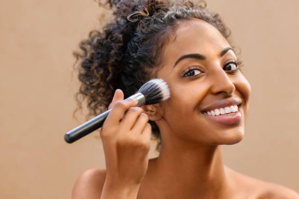 Black beauty woman using makeup brush stock photo
