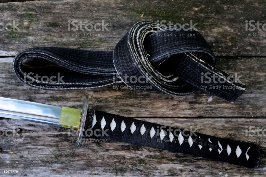 Black belt of martial arts and Japanese katana sword on old boards. stock photo