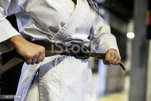Unrecognizable young woman exercising karate.