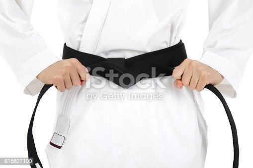 Young karate guy tying black belt, isolated on white background