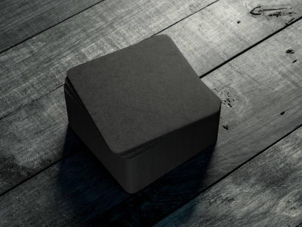 schwarze getränk bierdeckel mock-up auf dem holztisch - untersetzer stock-fotos und bilder