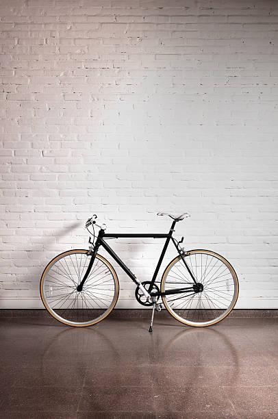 negro bicicleta sobre una pared de ladrillos - bastidor de la bicicleta fotografías e imágenes de stock