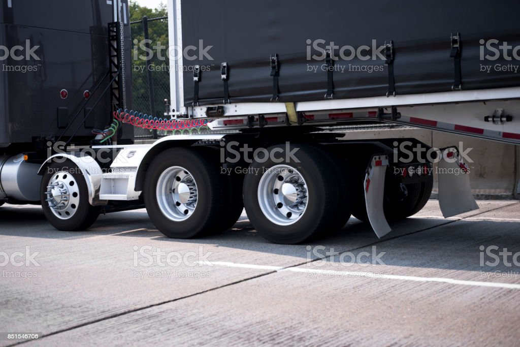 Black big rig semi truck with chrome wheels and fenders and black tented frame semi trailer going by roadway stock photo