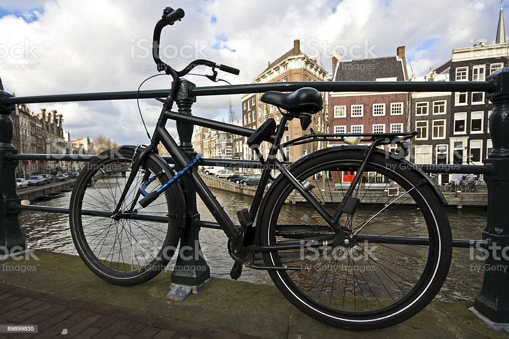 Black bike chained on a bridge in Amsterdam the Netherlands royalty-free stock photo
