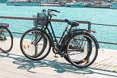 Black retro bicycle parked on the waterfront of the lake. Horizontally framed shot. Zero emission green eco energy