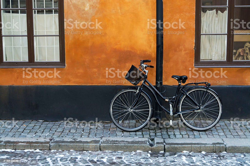 Black bike with basket on  red wall, Stockholm , Sweden stock photo