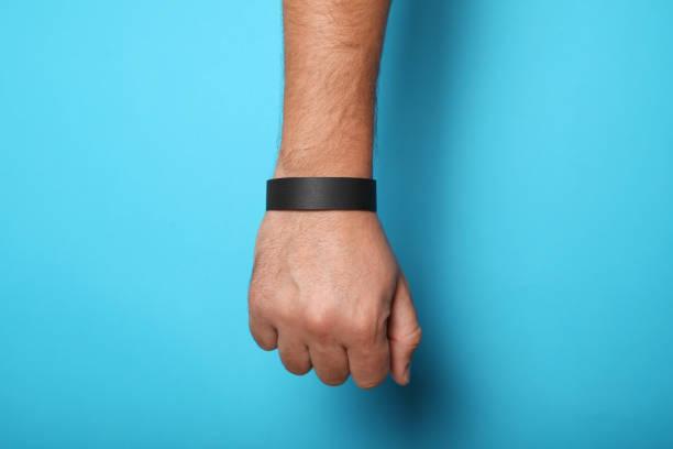 black blank bracelet on hand. music festival branding wristband, adhesive paper accessory for concert, event. mockup - браслет стоковые фото и изображения