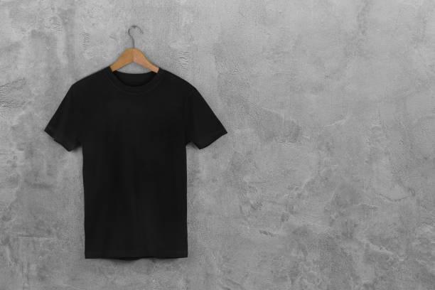 preto em branco camiseta de algodão pendurado centro de concreto cinza fundo vazio da parede - camiseta preta - fotografias e filmes do acervo