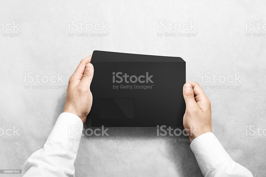 Black blank envelope mock up holding in hand. stock photo