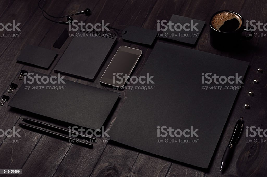Black blank stationery set with phone, earphone, coffee on dark wood background, inclined. royalty-free stock photo
