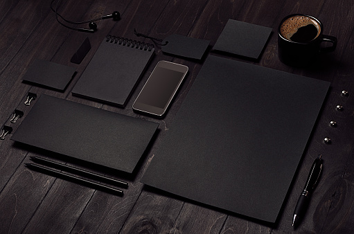 istock Black blank stationery set with phone, earphone, coffee on dark wood background, inclined. 945451566
