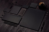 Black blank stationery set with phone, earphone, coffee on dark wood background, inclined.