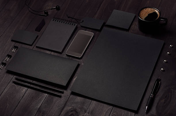 Black blank stationery set with phone, earphone, coffee on dark wood background, inclined. stock photo