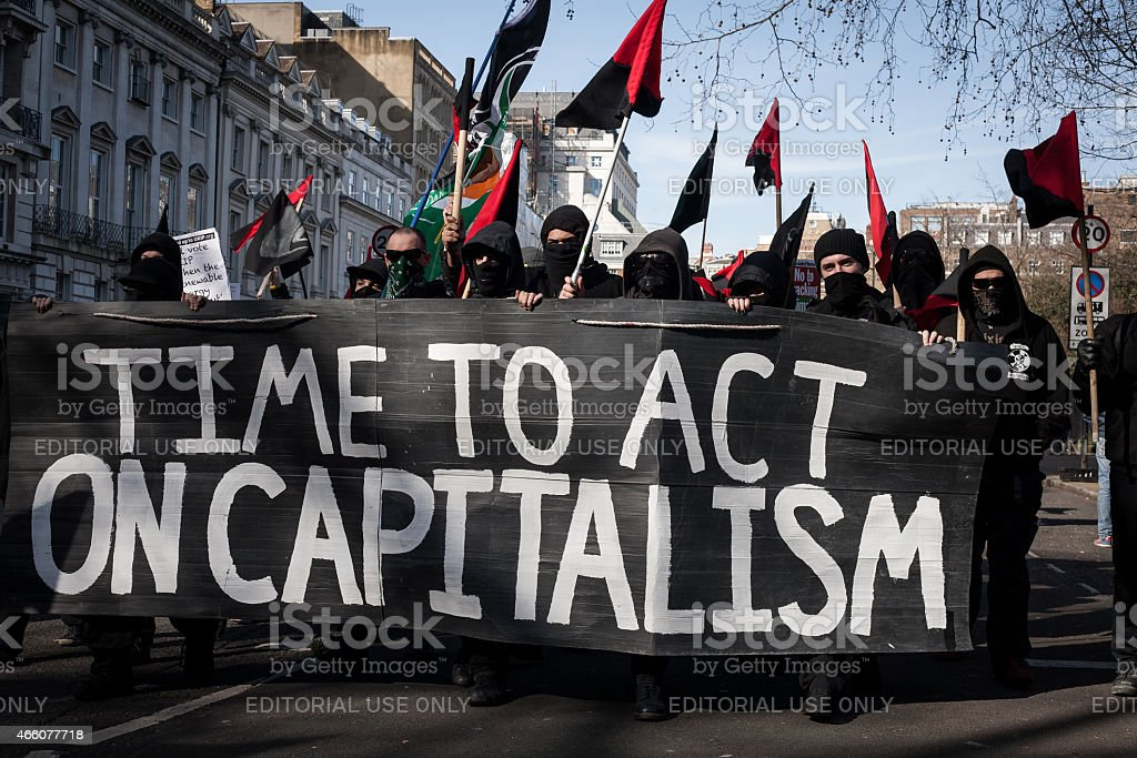 Black bloc anti-capitalist protesters march in London stock photo