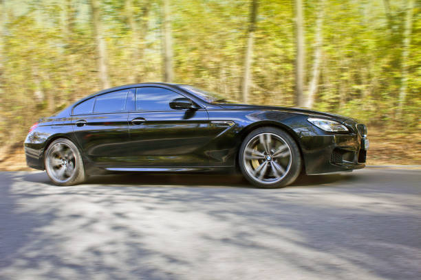 Black BMW M6 in autumn forest. BMW in motion stock photo