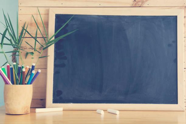 Schwarzes Brett und Stapel von Stift auf Holztisch. Bildungskonzept. – Foto