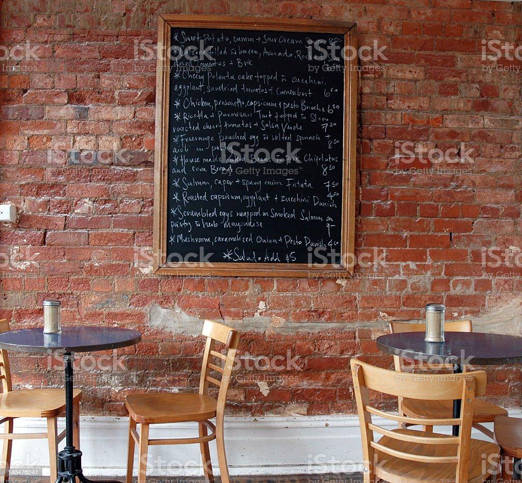 A black board restaurant menu against a brick wall stock photo