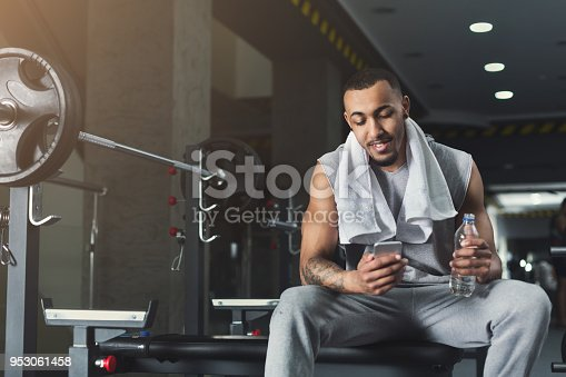istock Black bodybuilder using mobile phone at gym 953061458