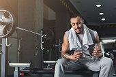 istock Black bodybuilder using mobile phone at gym 953061458