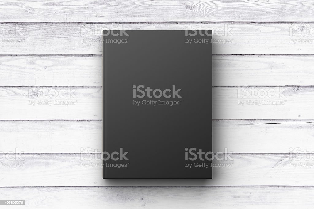 Black book cover on a white wooden surface, mock up stock photo