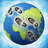 Black boots footprints on the globe harming continents and seas.\nAdobe Illustrator and Photoshop used for world texture map modifications. Original texture link: https://eoimages.gsfc.nasa.gov/images/imagerecords/73000/73580/world.topo.bathy.200401.3x5400x2700.jpg