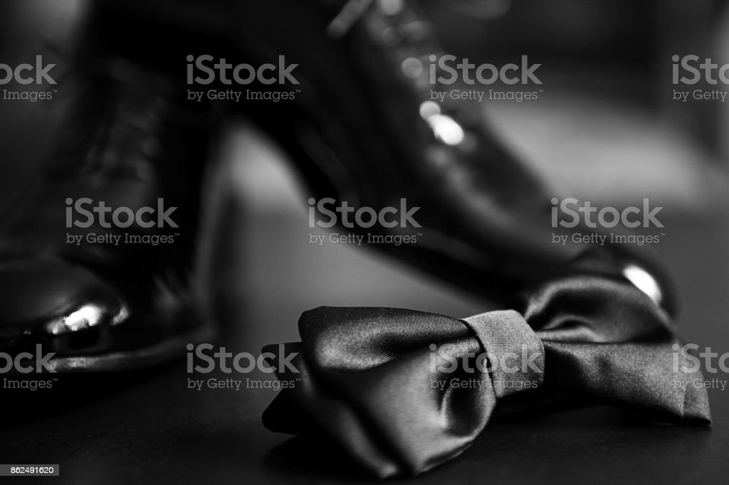 Black bow tie and black shiny shoes stock photo
