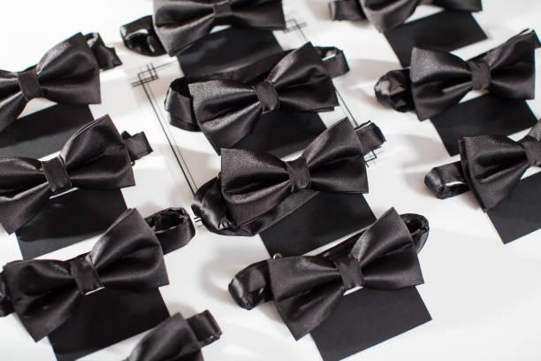 schwarze fliege. schwarze fliege auf einem weißen hintergrund. dresscode-party - hochzeitskleid in schwarz stock-fotos und bilder