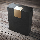 Black box with golden sticker on the wooden floor
