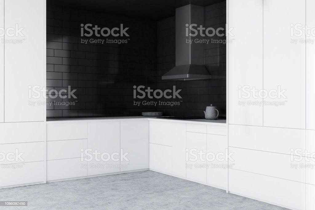 Corner of minimalistic kitchen with black brick walls, concrete...