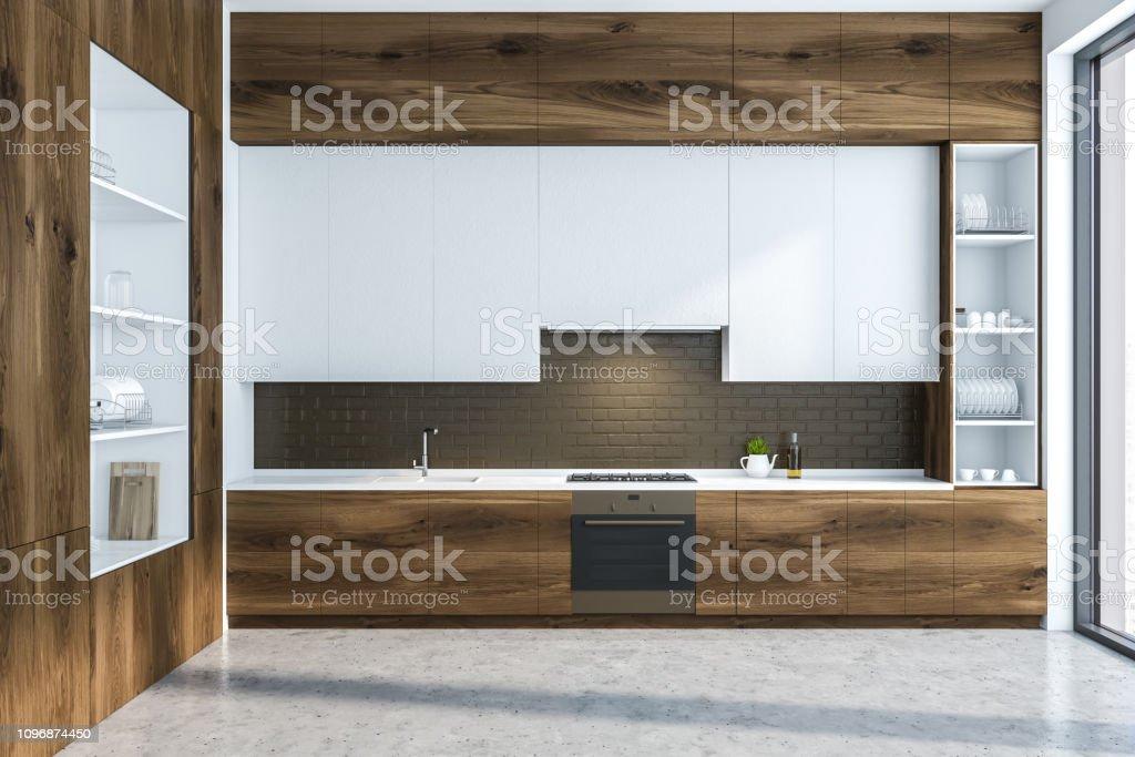 Interior of modern kitchen with black brick walls, concrete floor,...