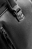 Close-up of a black briefcase (faux leather texture). Space for copy.