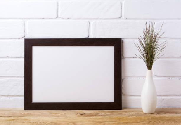Black brown  landscape frame mockup with dark grass in elegant vase stock photo